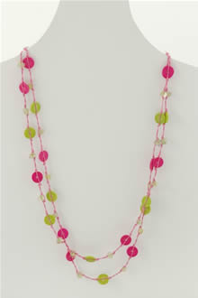 A long necklace of fuchsia and lime buttons on thread with clear glass beads